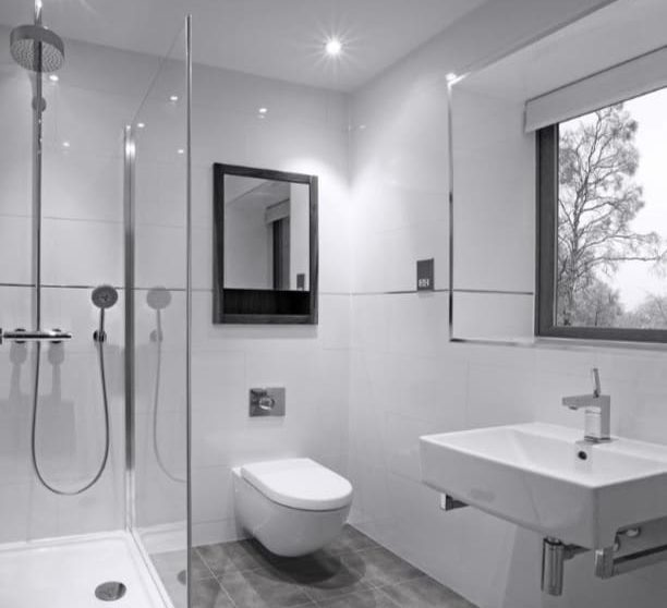 All white bathroom, shower on the left of the toilet, there is a mirror above the toilet and sink in front of it with a window above the sink, grey floor