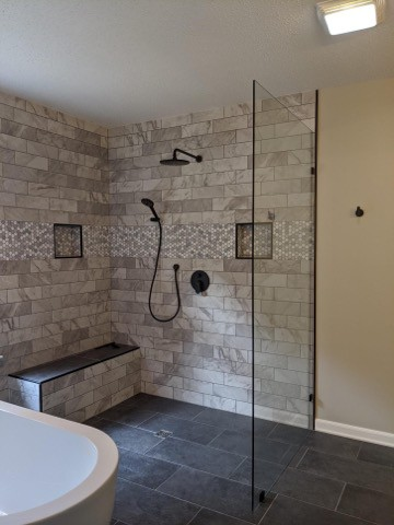 Bathroom with bathtub on the left and a black shower head to the right on a marble like brick wall design, a small seating ledge is in the shower