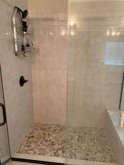 shower with a white brick patterned wall a black shower head with an accessory to hold shampoo etc hanging from it, the shower has a glass casing