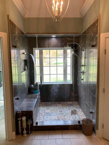 Huge marble walled shower with a chrome shower head on the right a waterfall shower head on the left, a marble bench is below the water fall as well as a ledge with shower products, there is a large window behind the shower and a chandelier above