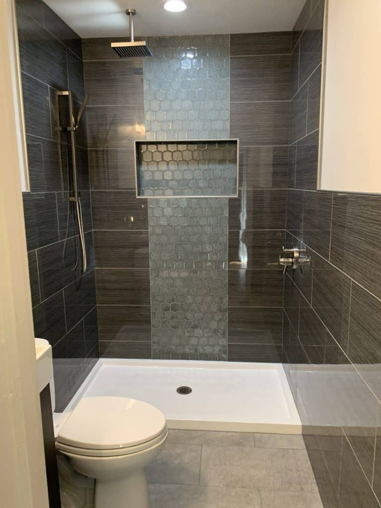 Dark grey walled bathroom with a shower head hanging directly from the ceiling directly in front and a toilet to the left