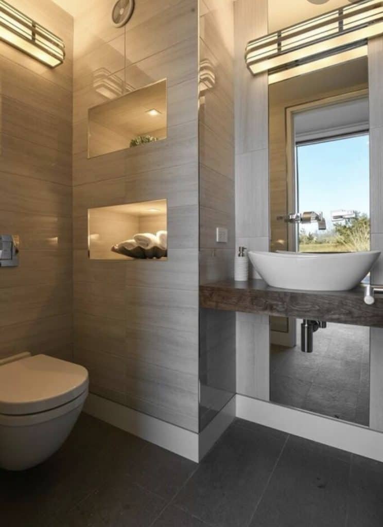 Modern grey bathroom, toilet is connected tothe wall on the left there are two shelves beside it with decorations to the right of these shelves is bowel sinkon a floating counter top in front of a very tall mirror