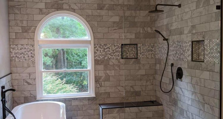 Bathroom with bathtub on the left wall and black shower head on the right, window is on the back marble like brick wall design , to the right of the window is a small seating ledge